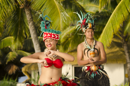 tahitian: Portrait of attractive young Polynesian Pacific Island Tahitian male and female dancers in colorful costumes dancing on tropical beach during sunset with palm trees in the background.