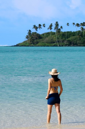rarotonga: Young happy woman looks at small Island and enjoys sunny day on Muri beach lagoon in Rarotonga, Cook Islands.