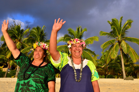 islanders: Portrait of two happy smily mature Polynesian Pacific islanders women on tropical beach with palm trees in the background. Photo have MR