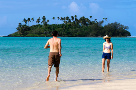 rarotonga: Attractive young man runs towards happy young woman on vacation on Muri beach lagoon in Rarotonga, Cook Islands.