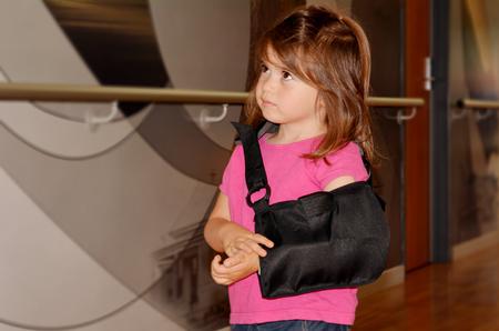 brazo roto: Ni�a triste con un brazo roto en el pasillo del hospital. Foto de archivo