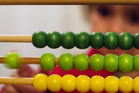 juguetes de madera: La niña aprende a contar y Calculat en la calculadora china con cuentas de colores - Close-up. Foto de archivo