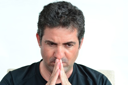 Mature man thinking with hands on his mouth looking down. close up on white background. real people. Concept photo of puzzled, confused, worried, problems, alone, thoughtful, worried, man Stock Photo