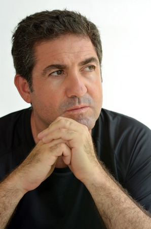 introspective: Mature man thinking with hands on chin looking away.close up on white background. real people. Concept photo of puzzled, confused, worried, problems, alone, thoughtful, worried, man Stock Photo
