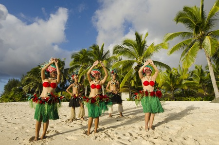 tahitian: Group portrait of Polynesian Pacific Island Tahitian dance group in colorful costumes dancing on tropical beach with palm trees in the background. Stock Photo