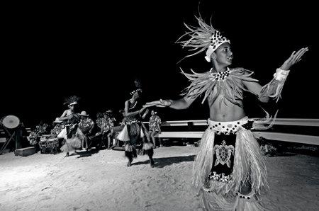 tahitian: Polynesian Pacific Island Tahitian male dancers in costume dancing on tropical beach. (BW) Editorial