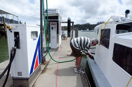 Bank Światowy: BAY OF ISLANDS, NZ - DEC 12:Man fuels his boat on Dec 12 2013.According to the world bank the pump price for diesel fuel in NZ in 2013 is 1.24 (US $ per liter) Publikacyjne