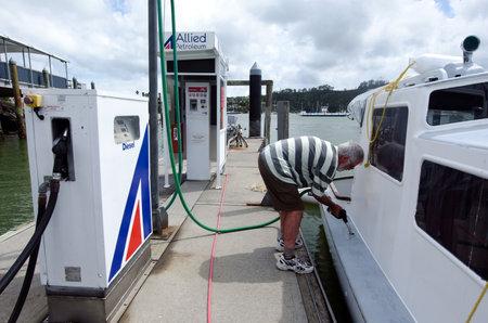 banco mundial: Bay of Islands, Nueva Zelanda - 12 de diciembre: Los combustibles hombre su barco el 12 dic 2013.According al banco mundial del precio de la bomba de combustible diesel en Nueva Zelanda en 2013 es 1,24 (US $ por litro)