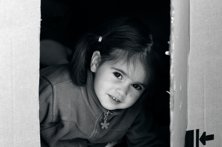 moving box: Portrait of a girl in a cardboard box during house moving. concept photo