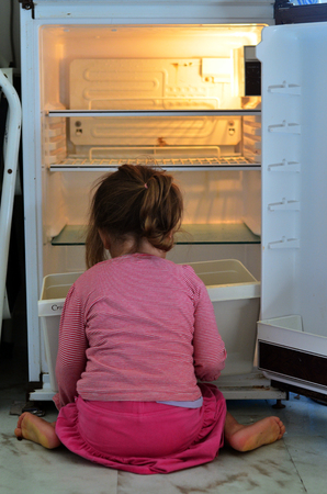 Hungry Poor little girl look for food in empty fridge at home.