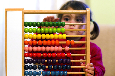 Little girl learns to count and calculat on Chinese calculator with colorful beads - Close-up   . Stock Photo