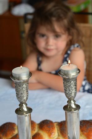 sabbath: Jewish girl looks at lit sabbath candles before shabbat eve dinner. Stock Photo