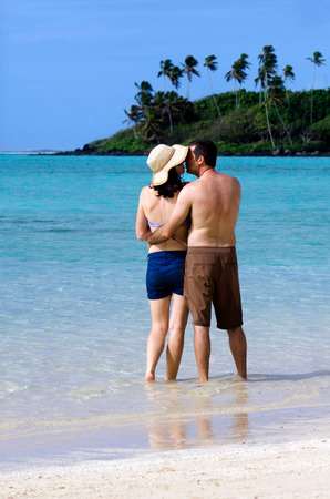 rarotonga: Attractive young happy couple on vacation hugs and kisses on Muri beach lagoon in Rarotonga, Cook Islands. Stock Photo