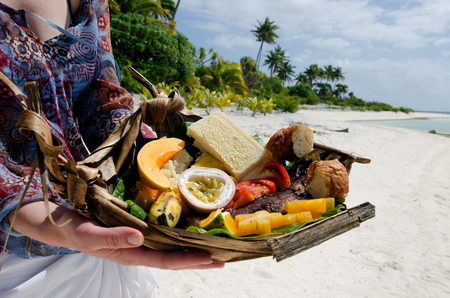 island: Young woman hands carry tropical food of grilled fish, fruits and vegetables dish served on deserted tropical island in Aitutaki lagoon, Cook Islands. Stock Photo