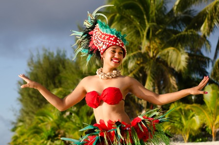 island: Portrait of Polynesian Pacific Island Tahitian female  dancer  in colorful costumedancing on tropical beach with palm trees in the background.