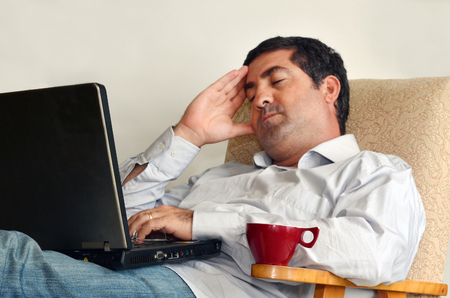 tired worker: Tired man that works from home sleeps in front of his laptop.Concept photo of working from home, home jobs,distance education, distance learning. Stock Photo