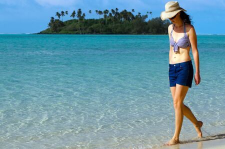 rarotonga: Young happy woman on vacation walks on Muri beach lagoon in Rarotonga, Cook Islands.