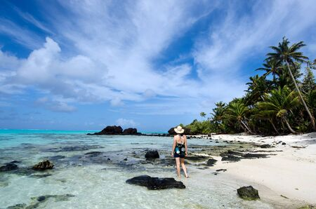 castaway: Tourist woman explores the nature and landscape of Aitutaki Lagoon Cook Islands.