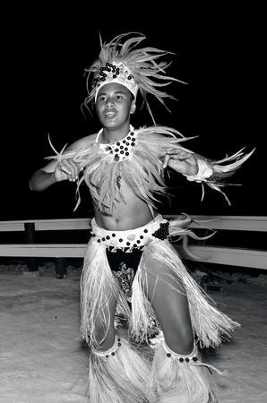 tahitian: Polynesian Pacific Island Tahitian male dancer in costume dancing on tropical beach. (BW)