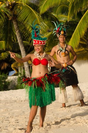 tahitian: Portrait of attractive young Polynesian Pacific Island Tahitian male and female dancers in colorful costumes dancing on tropical beach during sunset with palm trees in the background. Photo have MR Stock Photo