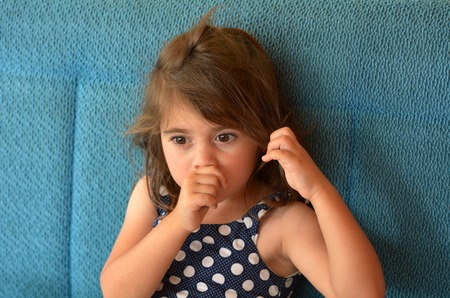 Little girl (age 3-4) sucks thumb at home. Concept photo of healthcare and early childhood Banque d'images