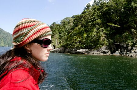 fiordland: Young woman sail on a cruise boat in Milford sound, Fiordland, New Zealand.