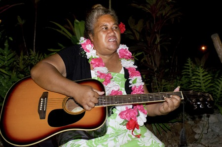 tahitian: Portrait of Polynesian Pacific Island Tahitian mature female sing a song and play music with Guitar on tropical beach in Aitutaki lagoon Cook Islands. Stock Photo