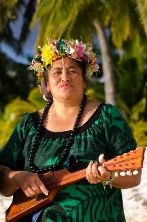 acoustic ukulele: Portrait of mature Polynesian Pacific islanders woman sing and plays Tahitian Music with Ukulele guitar on tropical beach with palm trees in the background (Photo have MR) Stock Photo