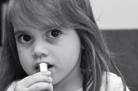 psicologia infantil: Niño (niña de 3 años de edad) aplicar el lápiz labial mirando a la cámara. Foto del concepto de niño, niña, la infancia, la apariencia, la curiosidad, la feminidad, el juego de simulación, función social, la psicología del niño. (BW) Foto de archivo