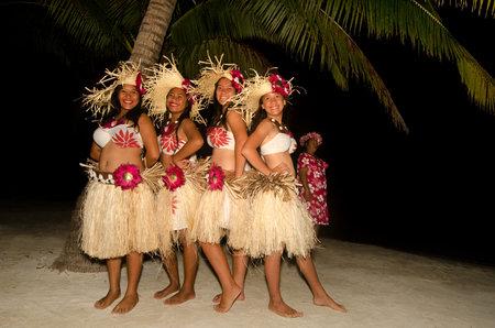tahitian: Portrait of young Polynesian Pacific Island Tahitian women dancers in colorful costume dancing on tropical beach.