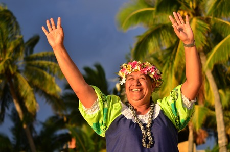 smily: Portrait of happy smily mature Polynesian Pacific Islander woman on tropical beach with palm trees in the background. Stock Photo