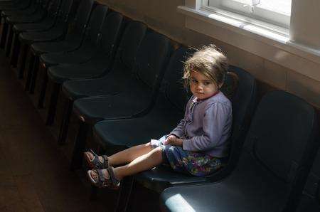 어린 소녀는 초등학교의 빈 복도에 의자에 앉아있다. 스톡 콘텐츠