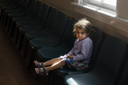 Little girl sit on a chair in empty hallway of a primary school. Banque d'images