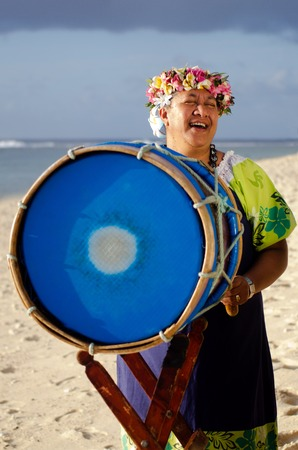 islanders: Portrait of mature Polynesian Pacific islanders woman sing and plays Tahitian Music with drum on tropical beach. (Photo have MR) Stock Photo