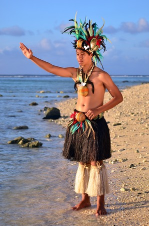 islanders: Portrait of attractive young Polynesian Pacific Island Tahitian male dancer in colorful costume dancing on tropical beach during sunset. (Photo have MR)