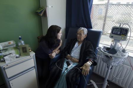 Sozialarbeiterin Besuch kranken alten männlichen Patienten im Krankenhaus.