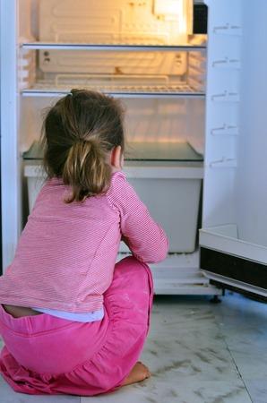 飢えた貧しい小さな女の子餌を探し空の冷蔵庫を自宅で。 写真素材