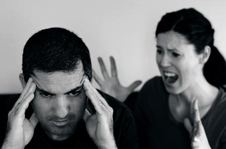 pareja discutiendo: Retrato de la joven pareja infeliz que han caído a lo largo de un desacuerdo que se sienta en un sofá. Hombre en la parte delantera y la mujer grita en el fondo. (BW)
