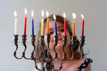 Happy Jewish girl look at fully lit Hanukkah menorah during the Jewish holiday of Hanukkah.