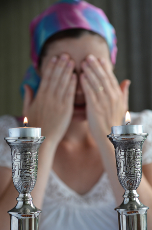 Jewish woman says the blessing upon lighting the sabbath candles before shabbat eve dinner. Stock Photo