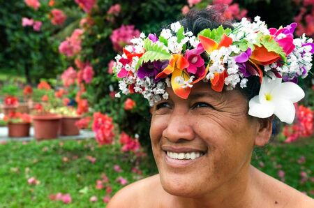 tahitian: Portrait of Polynesian Pacific Island Tahitian mature female wearing exotic flowers top bouquet smile in here home garden in Aitutaki lagoon Cook Islands.