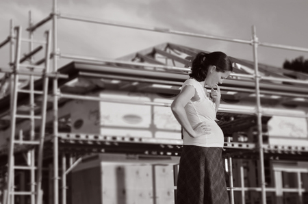 shure: Young pregnant woman worried outside here new home. Concept photo of buy a new home (BW)