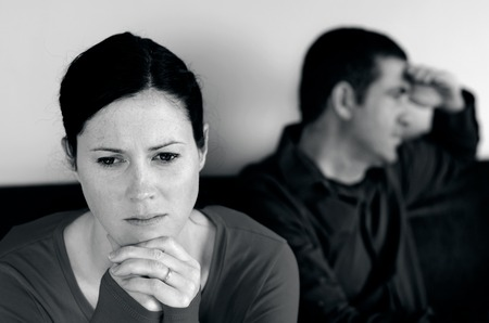 Portrait of unhappy young couple who have fallen out over a disagreement sitting on a sofa. Woman in the front and the man in the background.(BW)