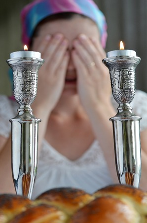 lit Shabbath kaarsen en ongedekte challah met een joodse vrouw die zegt dat de zegen op het aansteken van de sabbat kaarsen op de achtergrond, voor het diner shabbat vooravond.