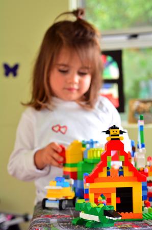 age 5: Child (Talya Ben-Ari age 3) plays in nursery room with Lego building bricks.Kids around the world spend around 5 billion hours playing with Lego.