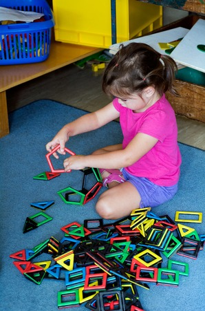 play room: Little girl play with building toy in a play room. Concept photo of preschool education of creativity and thinking
