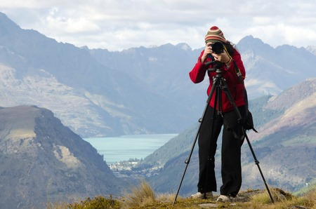 documenting: Professional on location and nature photographer (woman) photographing landscape  outdoor.