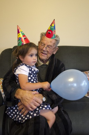 grandchild: Proud grandparent holds his grandchild during a birthday party.