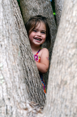 seek: Cute little girl is playing hide and seek outdoors.