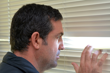 nosy: Man (age 35-40 ) looks out through Venetian blinds. Concept photo of curious, spy, nosy man.
